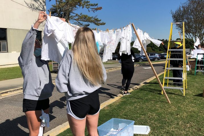 female students hang up shirts on clothesline