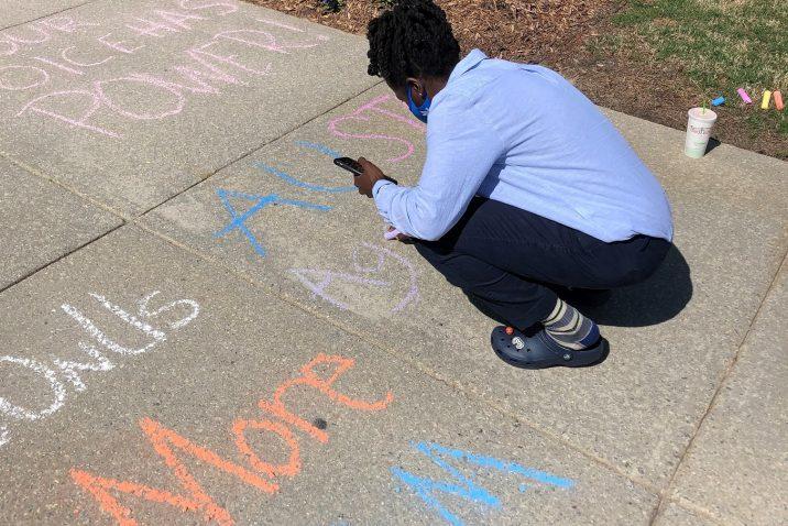 student writes slogan with sidewalk chalk