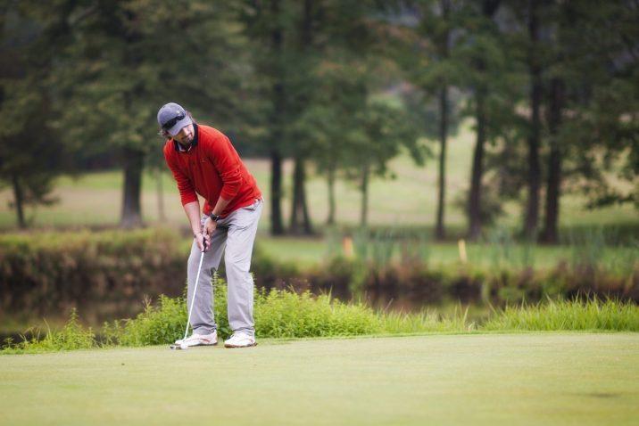 Golfer swinging at a ball.