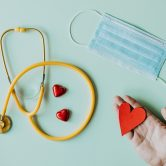Hand with paper heart, mask and stethoscope