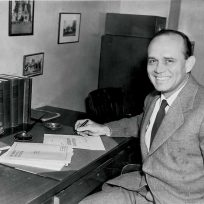 A man sitting down at a desk in a suit.