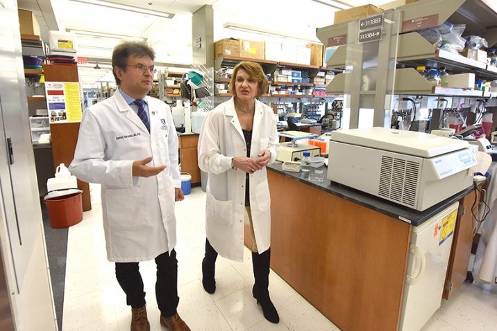 Two doctors (male on the left and female on the right) wearing white coats walk together through a lab