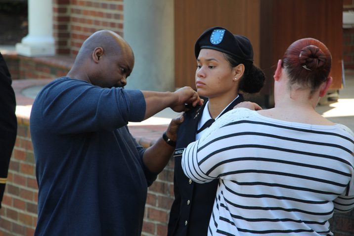 People pinning a woman cadet