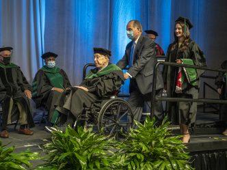 man pushing man in wheelchair