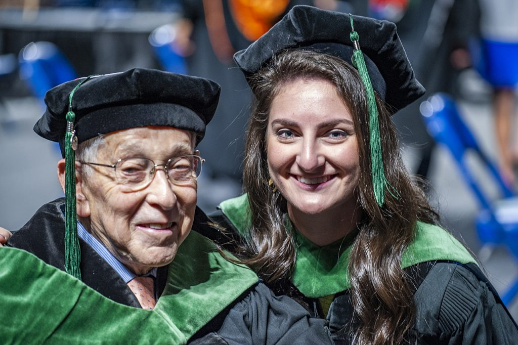 graduate and grandfather smiling