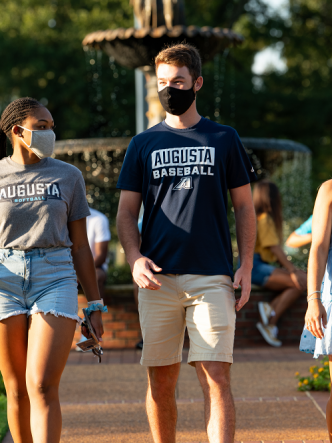 two women and one man, all wearing face masks, walking outside near a fountain