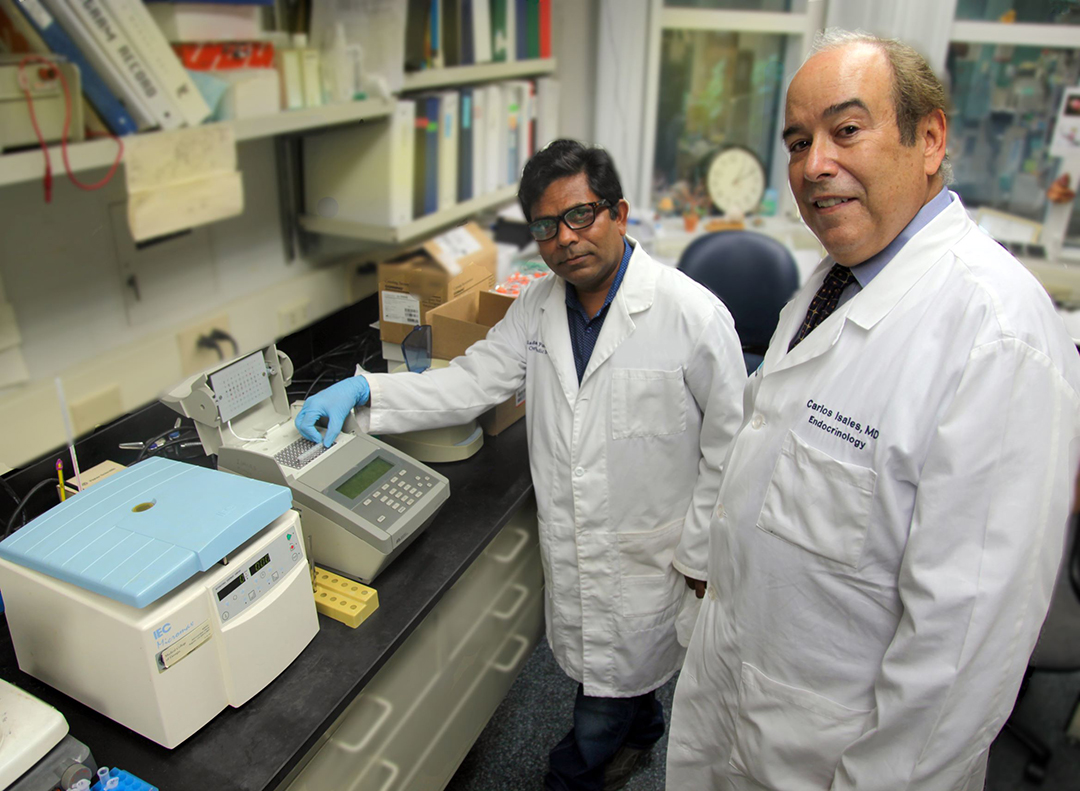Two men in white coats stand in a lab