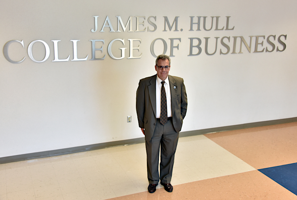 Dean of Hull College standing by sign.