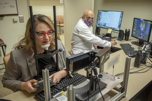 Woman with red glasses rests chin on machine used to break camouflage while a physician in a white coat looks on in the background