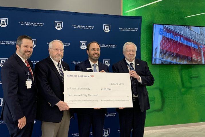 four men hold big check