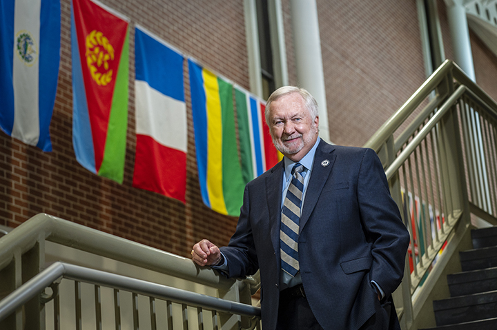 Man on stairs with flags in background