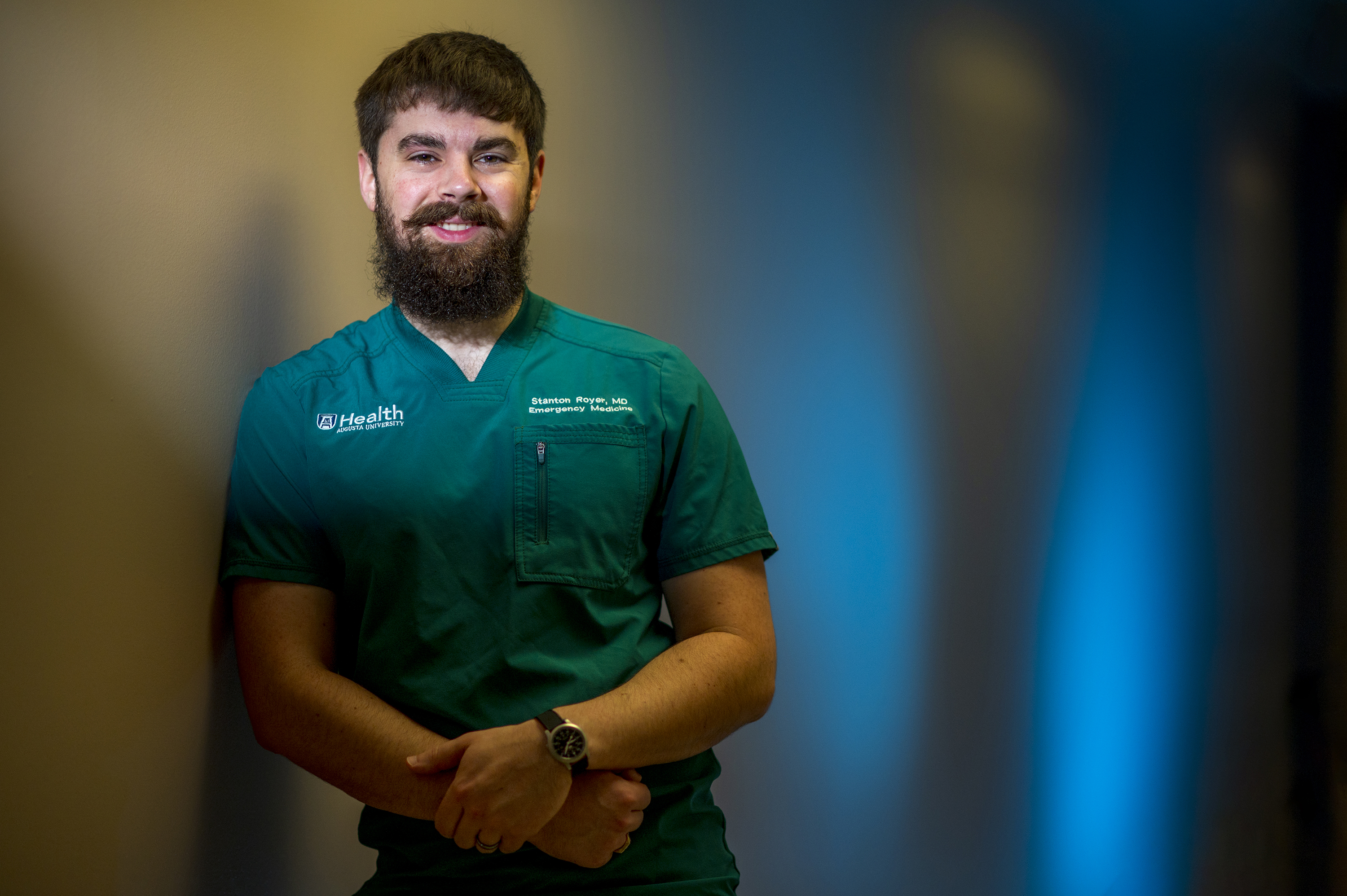 Man with beard in green scrubs look at the camera
