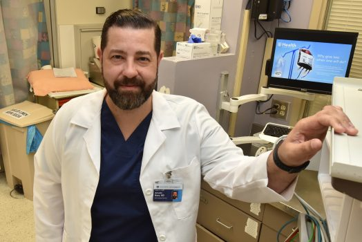Man with brown hair and beard, in white coat, stands in emergency room