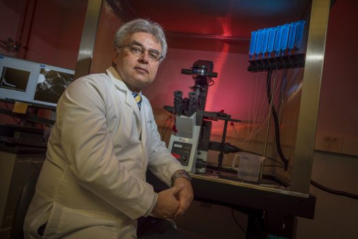 Gray haired man in white coat sits at lab bench with microscope in background
