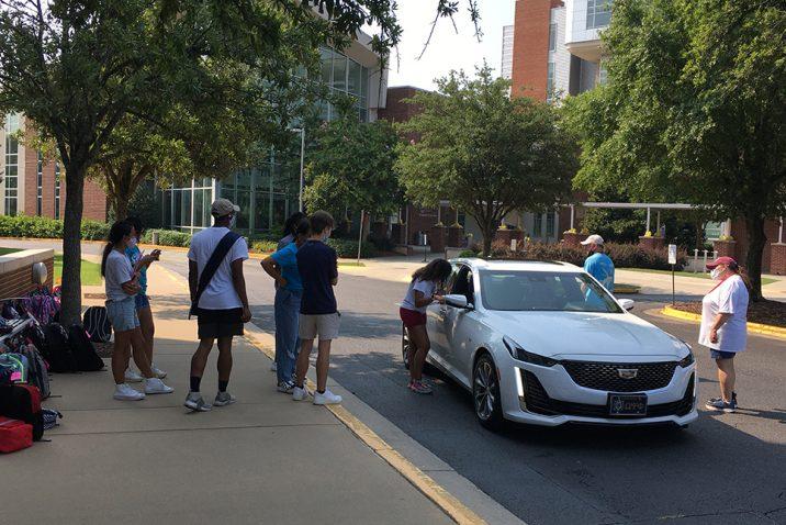Men and women standing near car