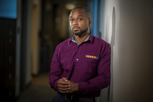 Young African American man in purple shirt stands in hallway looking at camera