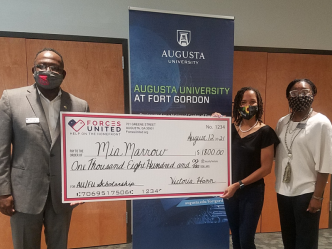 Three people holding check