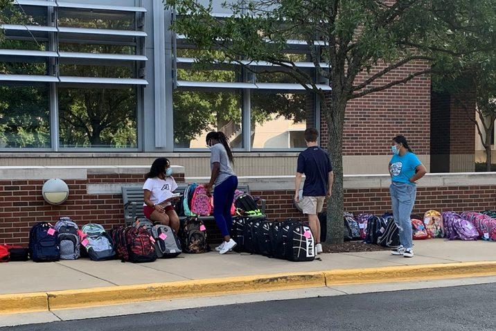 Men and women standing near backpacks