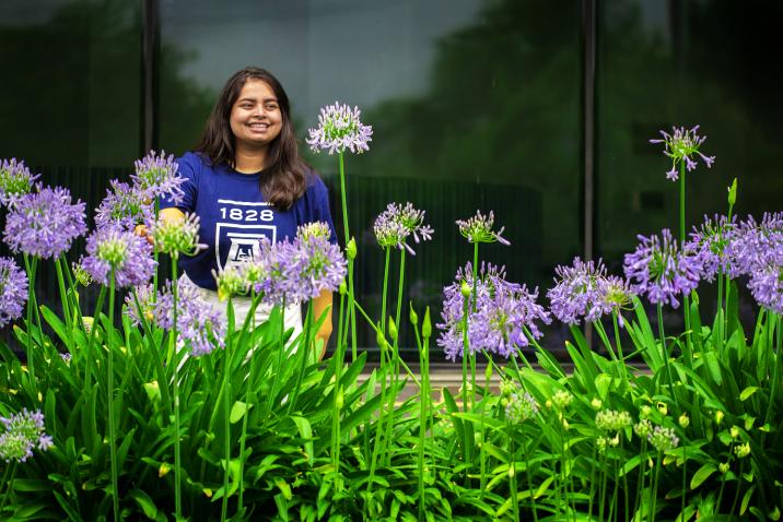 woman standing behind purple flowers