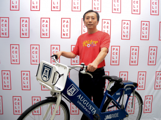 a man wearing a red T-shirt holds a blue and white bike
