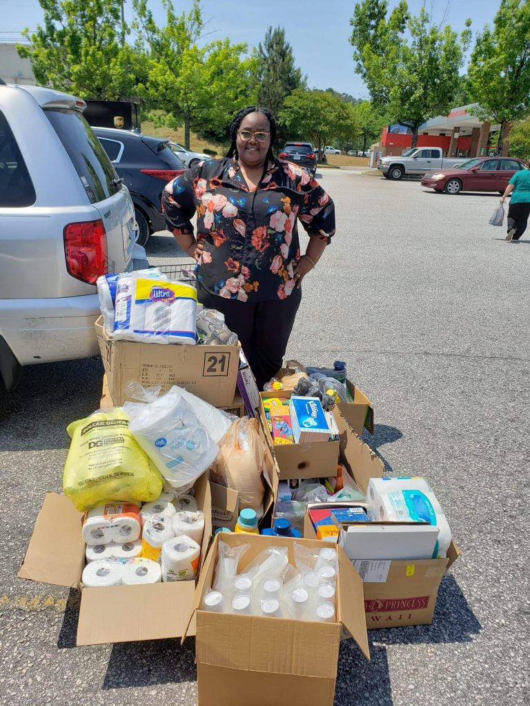 woman standing near boxes of food and supplies