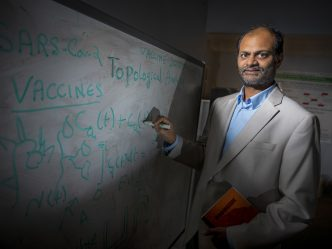 Man in cream jacket and blue shirt writes math equations on white board