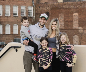 man and woman smiling for photo with 3 kids