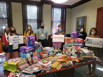 8 people, wearing masks, standing next to art supplies and toiletries