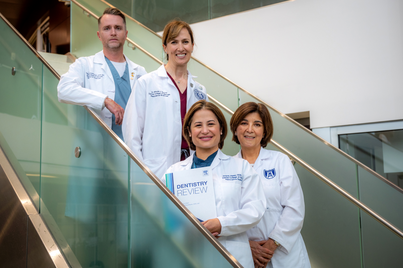 1 man and 3 women in whitecoats, standing on stairs