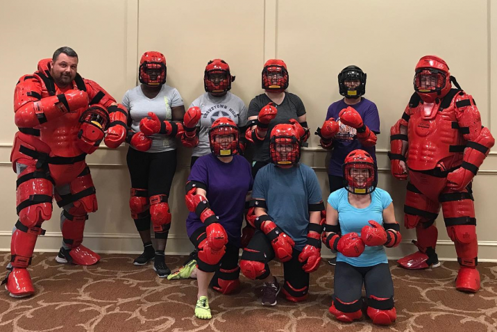 people wearing self-defense padding smile for a photo