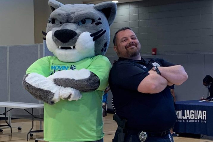 a police officer posing with Augusta University mascot