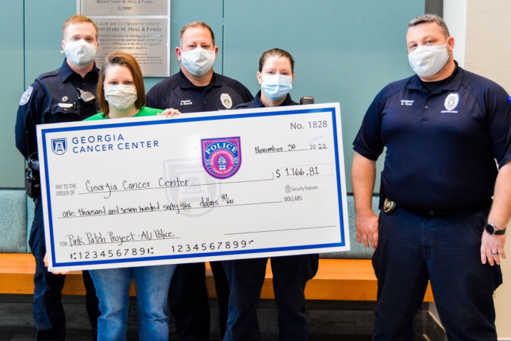 several masked people holding up a large check