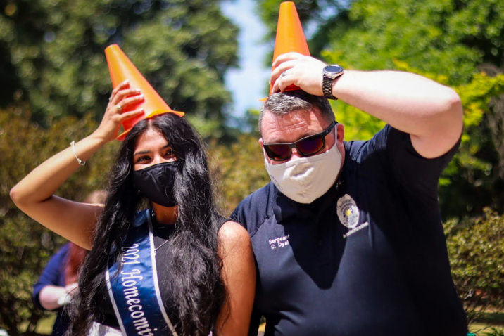 a woman and a male police officer wearing traffic cones like hats