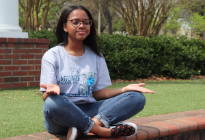 woman wearing glasses meditates outdoors