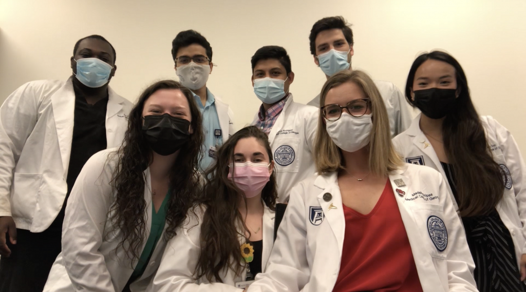 8 medical students wearing masks, smiling for picture