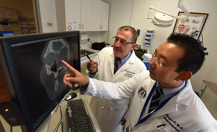 Two men with dark hair in white jackets, pointing at screen with skull xray