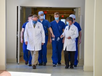 Two doctors in white coats lead a group of younger doctors in blue scrubs through a hospital hallway