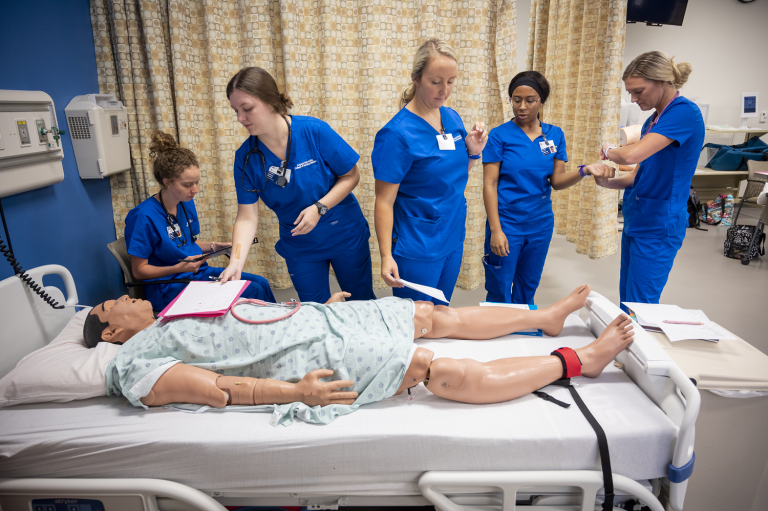 5 women nursing students standing over a mannequin
