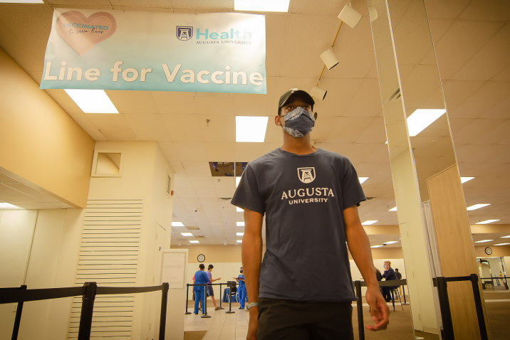 male student walking up to get his COVID-19 vaccine
