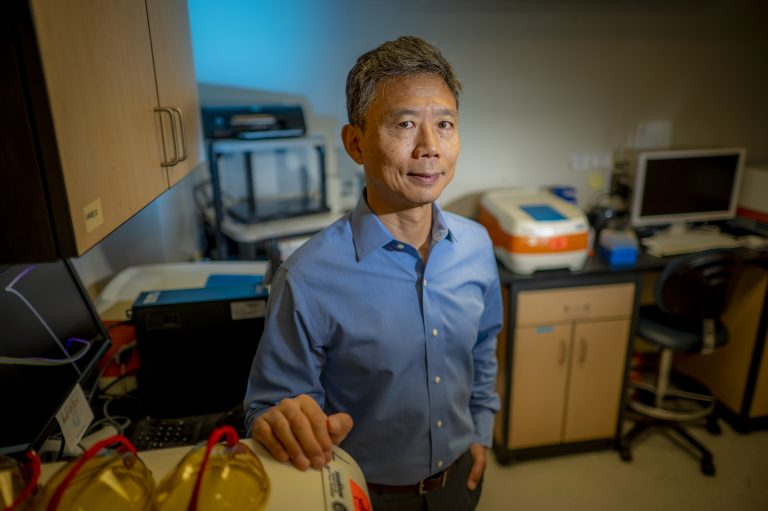 An Asian man in blue shirt stands in a lab