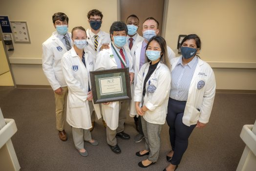 Group of masked people in white coats look at camera