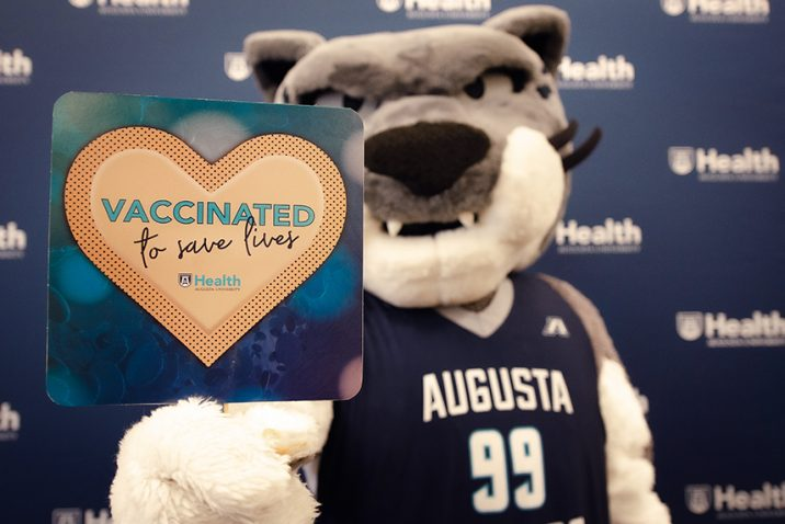 Mascot with sign: Vaccinated to Save Lives