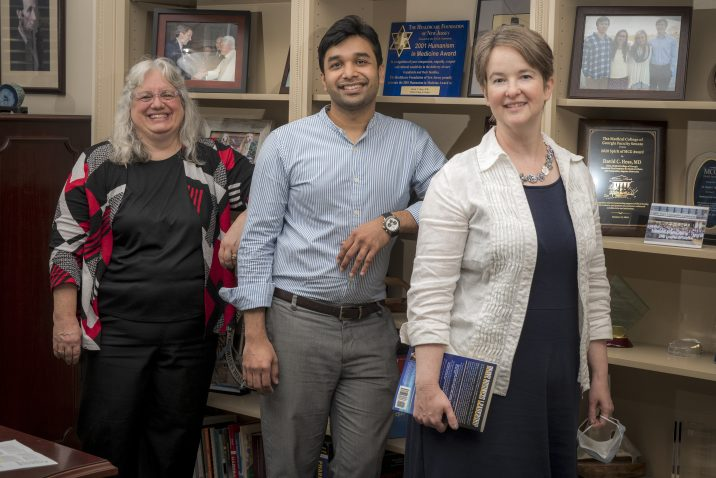 two women and man smile in front of bookshelf