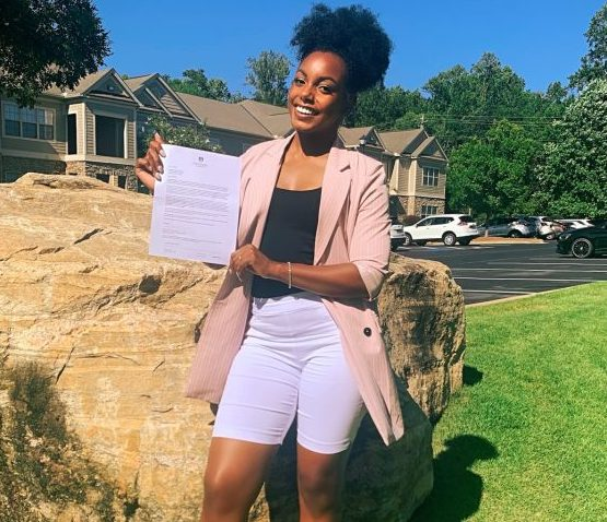 woman holding piece of paper and smiling