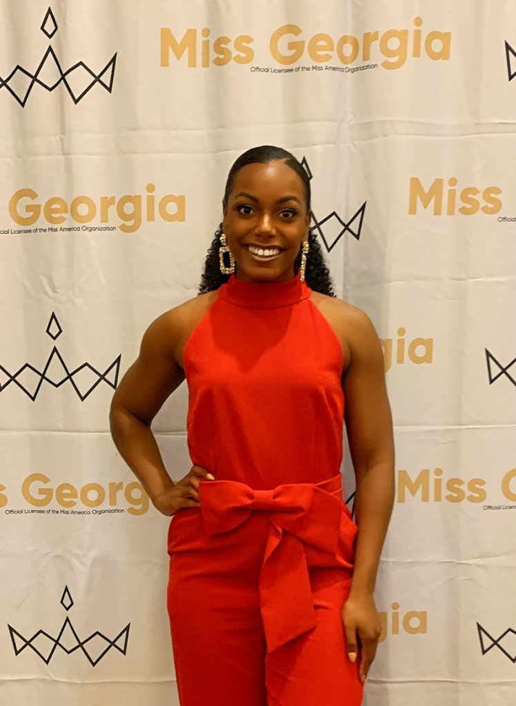"""woman wearing red romper in front of """"Miss Georgia"""" backdrop"""