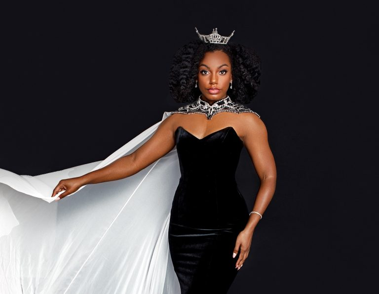 woman wearing black dress, white cape and crown
