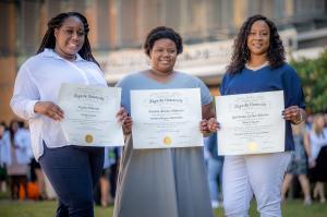 3 women holding diplomas