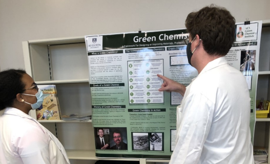 two people wearing lab coats looking at a poster