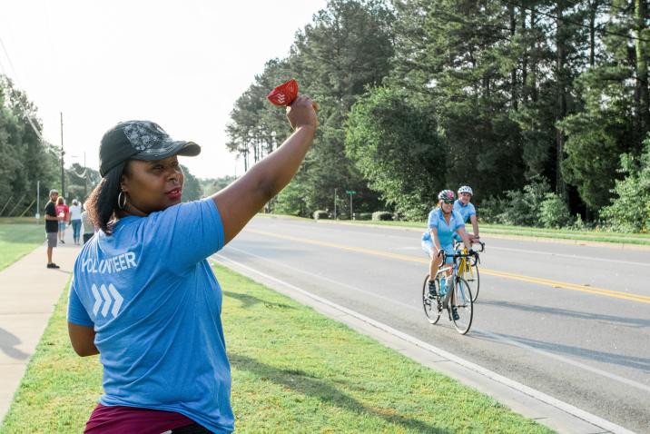 woman volunteer cheering on bikers