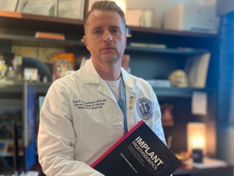 man in white coat holding textbook